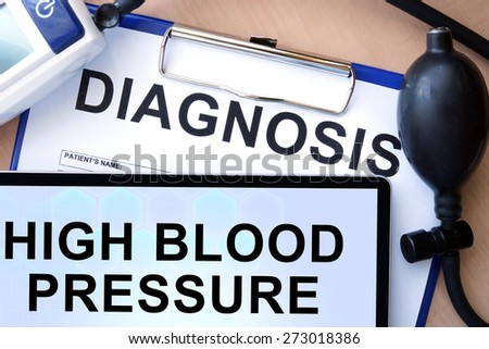 Tablet with  high blood pressure, form with word diagnosis and blood pressure meter  - stock photo