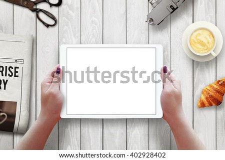 Tablet with isolated screen in woman hands. Morning time with newspaper, croissant, coffee on table. - stock photo