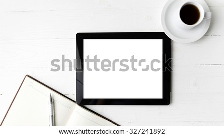 tablet with notebook and coffee cup over white table