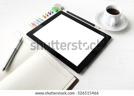 tablet with office supplies over white table
