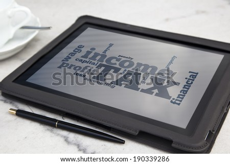 tablet with tax word cloud - stock photo