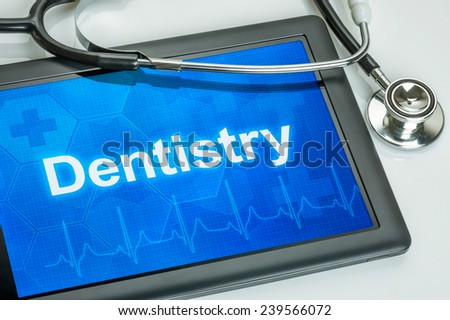 Tablet with the text Dentistry on the display - stock photo