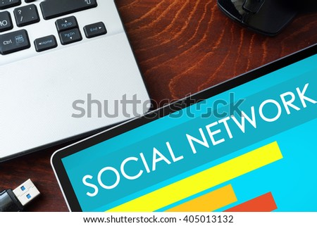 Tablet with words Social Network  on a wooden background.