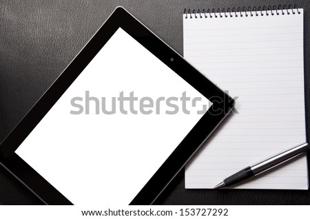 Tablet, writing pad and pen on a leather table top
