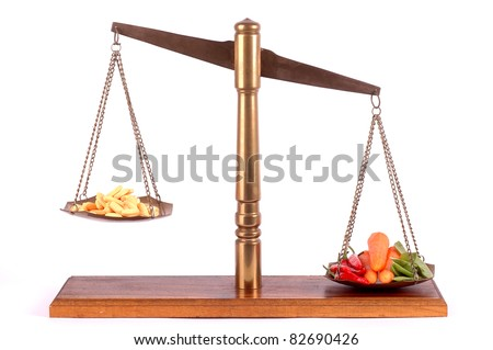 Tablets and fresh vegetables on a scale - stock photo