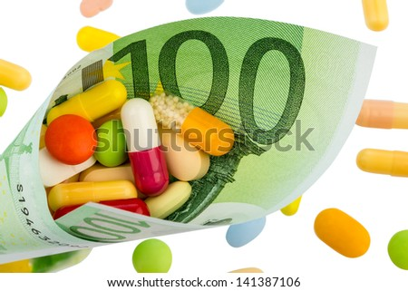 tablets and one hundred euro banknote symbolic photo: cost of medicine and drugs in the pharmaceutical industry - stock photo