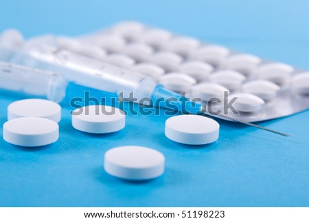 Tablets and syringes on a blue background