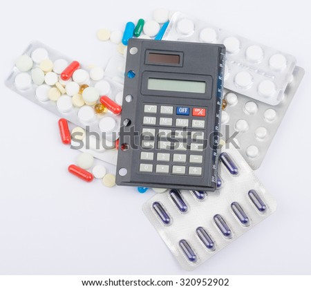 Tablets with capsules in blister packs and calculator lying on top. - stock photo