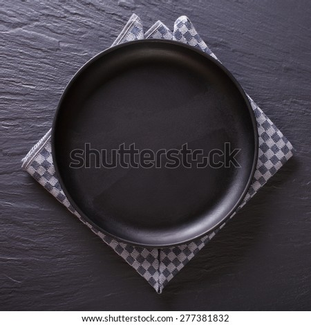 Tableware: black empty plate on the table. top view  - stock photo