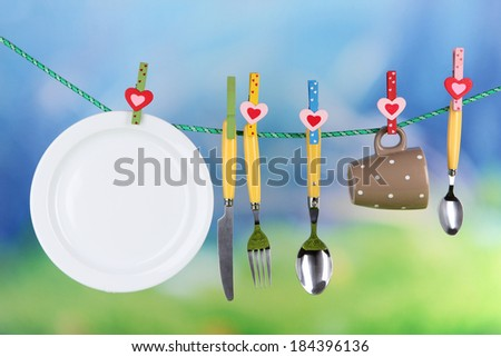 Tableware dried on rope on natural background - stock photo