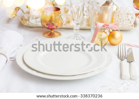 Tableware for christmas - set of empty plates  and utencils on white tablecloth with defocused lights in background - stock photo