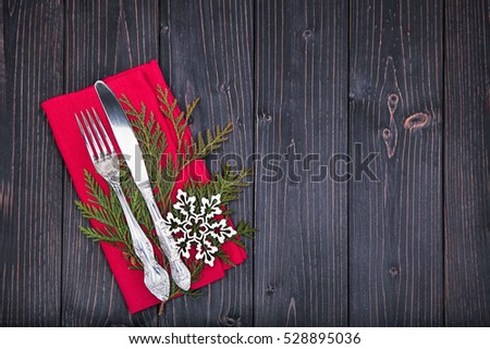 tableware on red linen napkin  decorated with fir-tree and woode