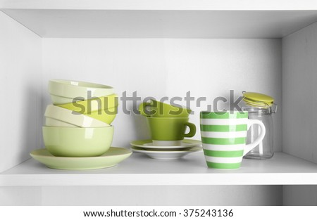 Tableware on shelf in the kitchen cupboard - stock photo