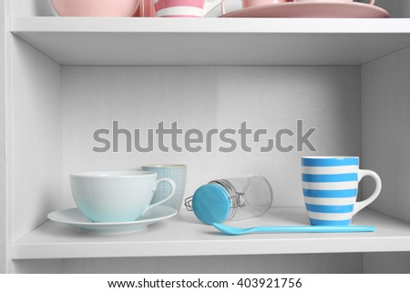Tableware on shelf in the kitchen cupboard - stock photo