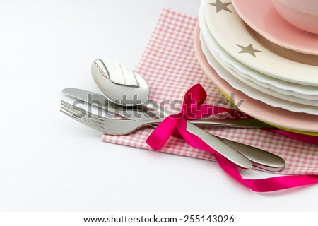 Tableware set: empty plates, fork and spoon decorated pink bow with ribbon on white  background - stock photo