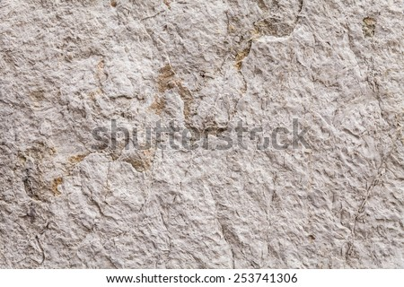 Tack sharp close up on the rough surface texture of an ancient stone wall. The weathered patina of the abrasive rock surface is streaked with thin fissures. Beige color. Plan view. Wide DOF. - stock photo