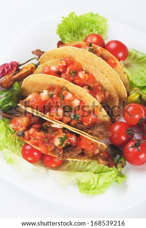 Taco shells filled with ground beef and fresh vegetable - stock photo