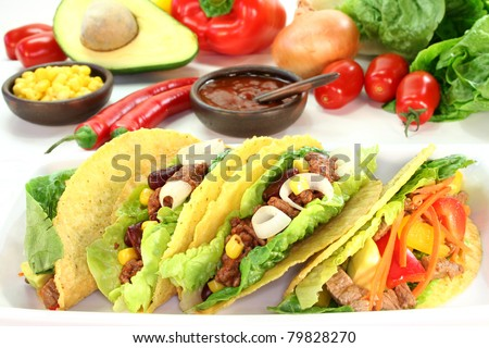 Taco shells filled with ground beef, kidney beans and corn - stock photo