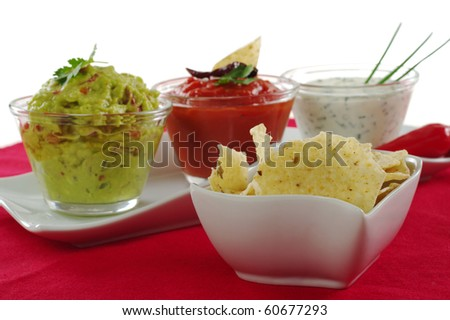 Tacos in bowl with three different dips (guacamole, tomato-chili dip and cream cheese dip) in the background on red tablecloth on white (Selective Focus) - stock photo