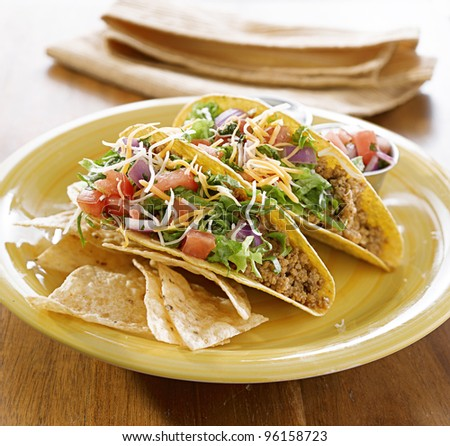 Tacos on a platter with tortillas shot with natural light - mexican food - stock photo