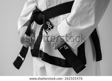 Taekwondo woman tying her black belt, 1e dan, and getting ready for training. - stock photo