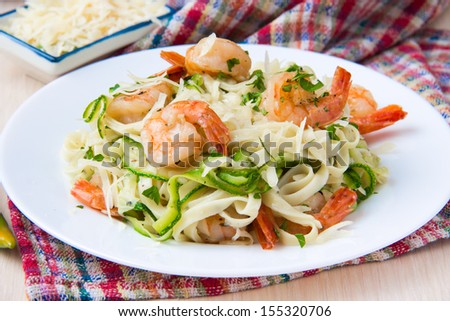 Tagliatelle pasta with fried shrimps, cheese Parmesan, parsley and zucchini ribbons, dish of restaurant - stock photo