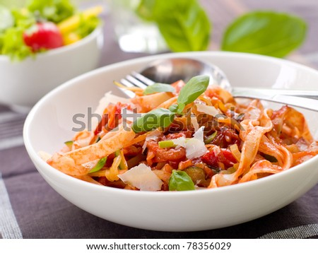 Tagliatelle pasta with tomato and vegetable sauce. Selective focus - stock photo