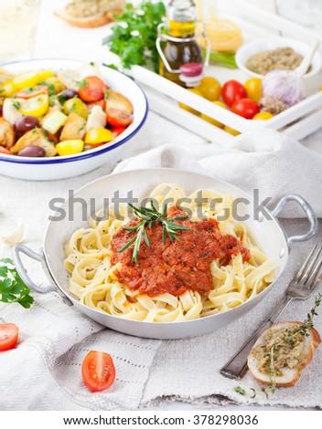 Tagliatelle pasta with tomato sauce and red pesto Italian cuisine - stock photo