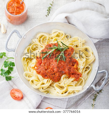 Tagliatelle pasta with tomato sauce and red pesto Italian cuisine Top view - stock photo