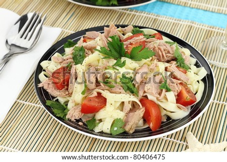 Tagliatelle pasta with tuna, parsley and cherry tomatoes - stock photo