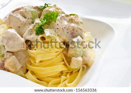 Tagliatelle pasta with white chicken zucchini sauce with nice copy space - stock photo