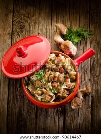 tagliatelle with edible mushroom and bacon over casserole - stock photo
