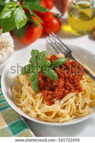tagliatelle with meat sauce garnished with basil leaves