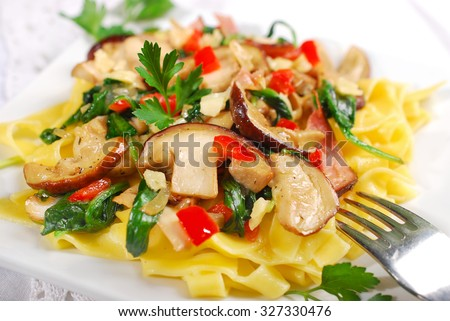 tagliatelle with  porcini mushrooms,baby spinach,bacon and cheese - stock photo