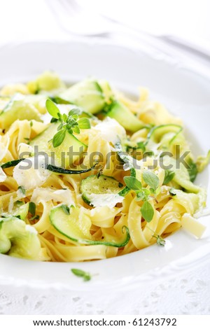 Tagliatelle with zucchini and Parmesan on a white plate - stock photo