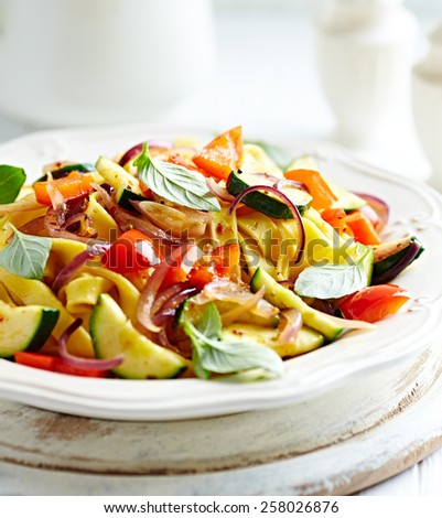 Tagliatelle with zucchini, pepper and red onion  - stock photo