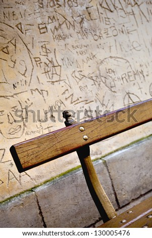 Tags and graffiti on the wall of a place and bench in the foreground