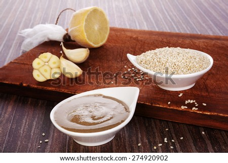 Tahini pasta in bowl, sesame seeds and lemon on brown wooden background. Culinary eating.  - stock photo