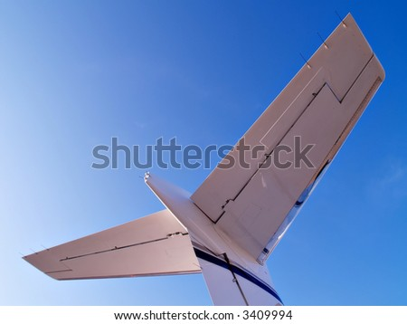 Tail of a business jet reaches into a blue sky - stock photo