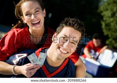 Tailgate: Smiling Man Hold Girl With Tickets Piggyback - stock photo