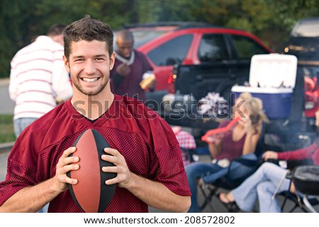 Tailgating: Smiling Fan Holding Ball After Team Win - stock photo
