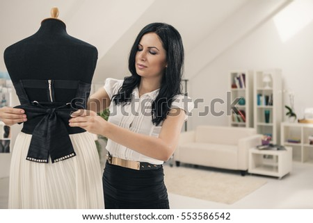 Tailor adjusting a dress on a mannequin at her studio.
