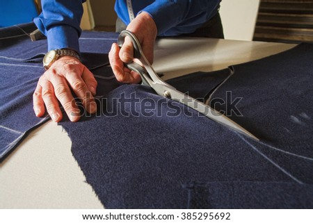Tailor Cutting Fabric to a New Coat with Scissors.