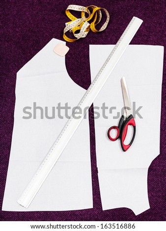 tailor instruments and pattern cut of woollen dress on cutting table - stock photo