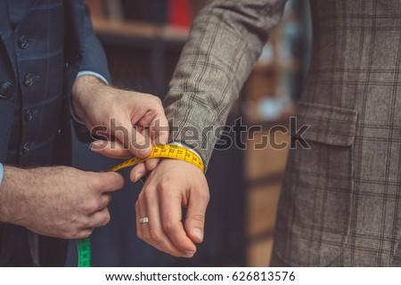 Tailor measures a man's hand