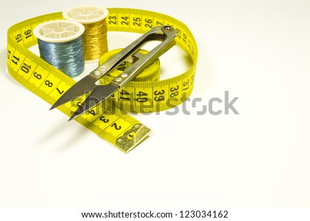 Tailor meter and a thread on a white background