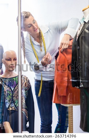 Tailor or shopkeeper displaying fashion in shop window - stock photo