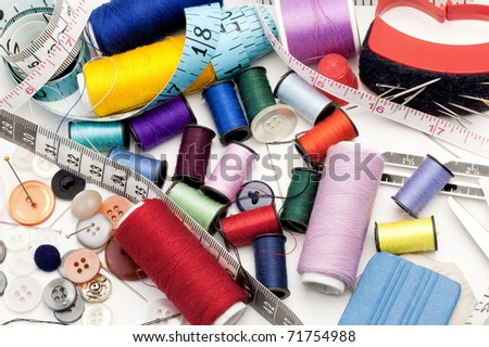 Tailor's Tools - Colorful Threads, Needle, Measuring Tape, Buttons - stock photo