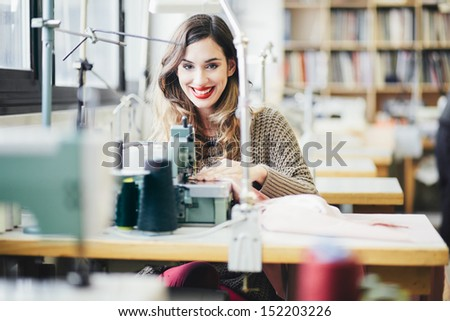 Tailor working in the shop using industrial grade tailoring machine - stock photo