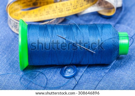 tailoring still life - thread bobbin with needle, button, measure tape on blue silk cloth - stock photo